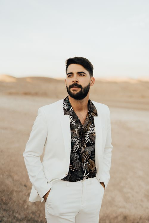 Stylish groom in white suit and patterned black shirt