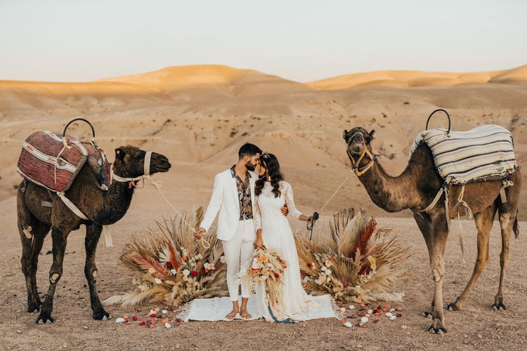 Bride and groom posing with camels at Moroccan desert wedding
