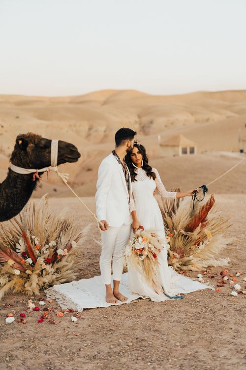 Bride and groom portrait with camels at Marrakesh desert elopement
