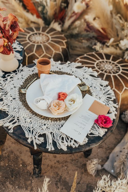 Pace setting with serving platter, macrame table cloth and pouffes