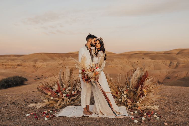 Boho bride and groom standing at the pampas grass and rug altar