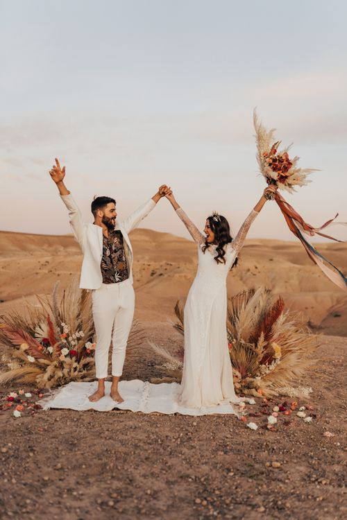 Stylish bride and groom at Moroccan wedding  in the dessert