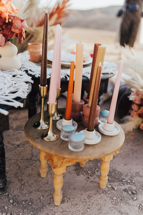 Coloured taper candles in rust, blush and neutral tones
