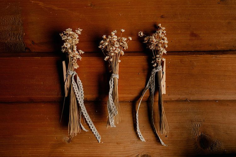 Dried flower buttonholes tied with lace