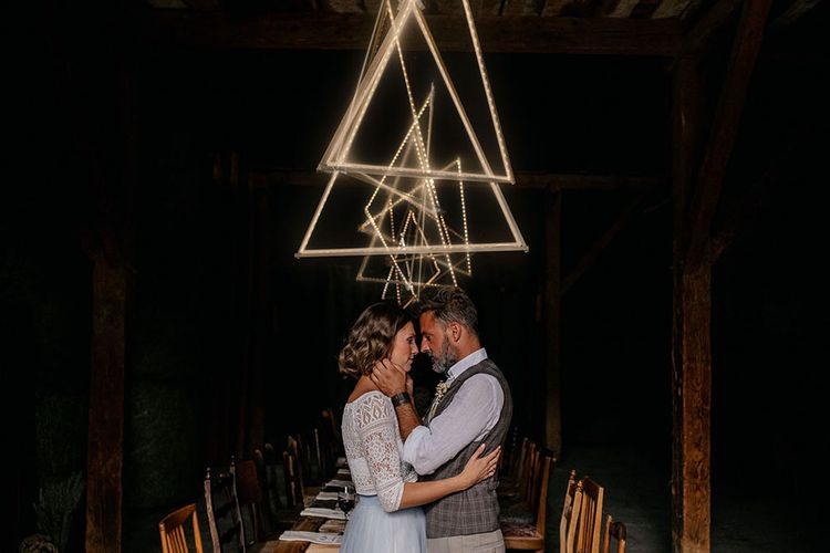 Bride and groom standing in front of triangle light installation