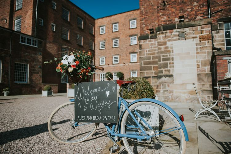 Vintage Bicycle & Chalkboard Welcome Sign Wedding Decor | Copper & Greenery Industrial Winter Wedding at The West Mill Derby, Styled by The Vintage House That Could | Rosie Kelly Photography | Jason Lynch Weddings
