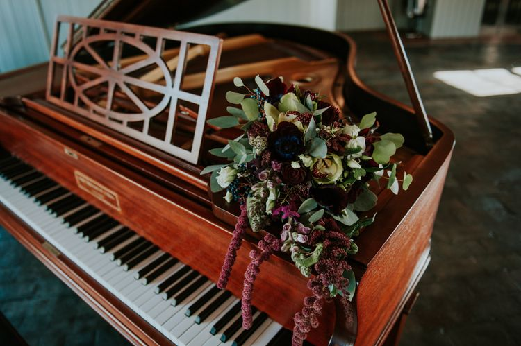 Winter Bouquet on Piano | Copper & Greenery Industrial Winter Wedding at The West Mill Derby, Styled by The Vintage House That Could | Rosie Kelly Photography | Jason Lynch Weddings