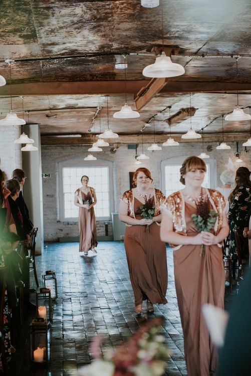 Wedding Ceremony Bridesmaid Entrance in Bronze ASOS Dresses | Copper & Greenery Industrial Winter Wedding at The West Mill Derby, Styled by The Vintage House That Could | Rosie Kelly Photography | Jason Lynch Weddings