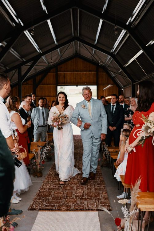 Bride walks down the aisle at The Giraffe Shed decorated in Autumn wedding colours