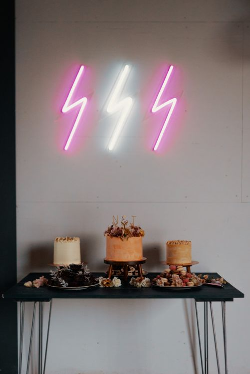 Neon wedding signs above cake table