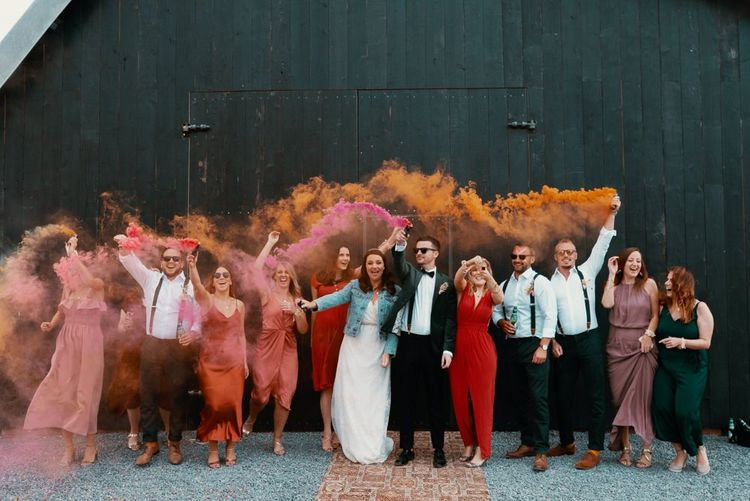 Guests wave smoke flares in Autumn wedding colours