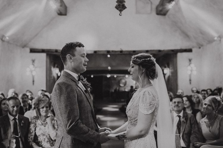 Wedding Ceremony with Bride in Beaded Jenny Packham Nashville Wedding Dress and Groom in Grey Check Blazer and Waistcoat Holding Hands