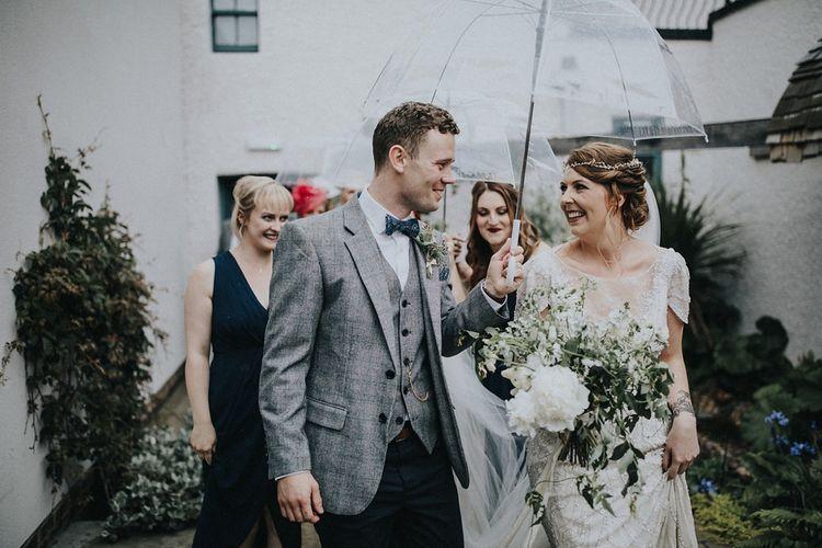 Bride in Beaded Jenny Packham Nashville Wedding Dress and Groom in Grey Check Blazer Under and Umbrella