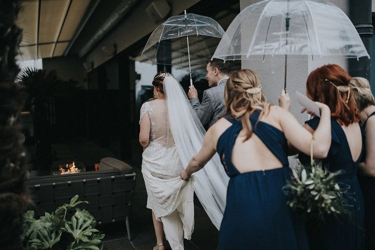 Bridesmaid in Navy Dress Holding Up The Brides Wedding Train