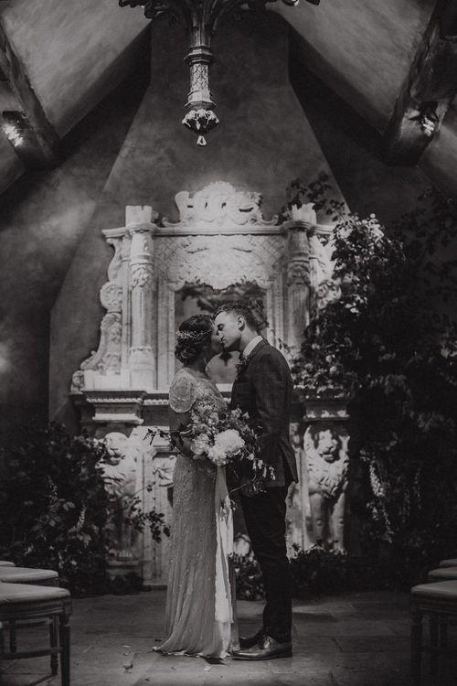 Bride in Beaded Jenny Packham Nashville Wedding Dress and Groom in Grey Check Blazer Kissing