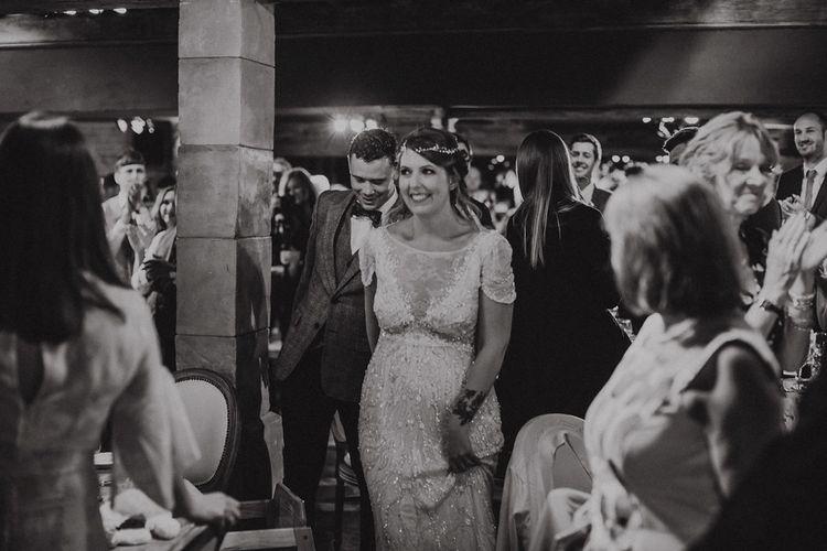 Bride in Beaded Jenny Packham Nashville Wedding Dress and Groom in Grey Check Blazer Entering The Wedding Breakfast