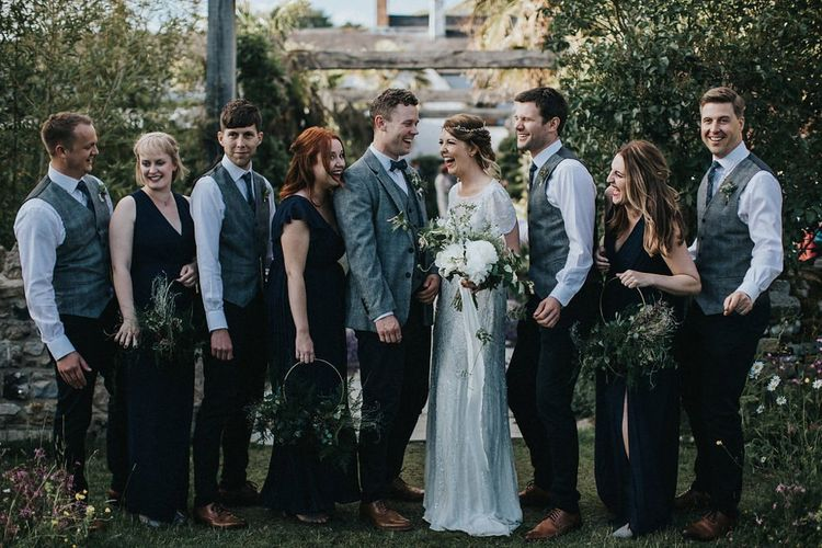 Wedding Party Portrait with Bridesmaids in Navy Dresses, Bride in Jenny Packham Nashville Wedding Dress and Groomsmen in Grey Check Blazers and Waistcoats