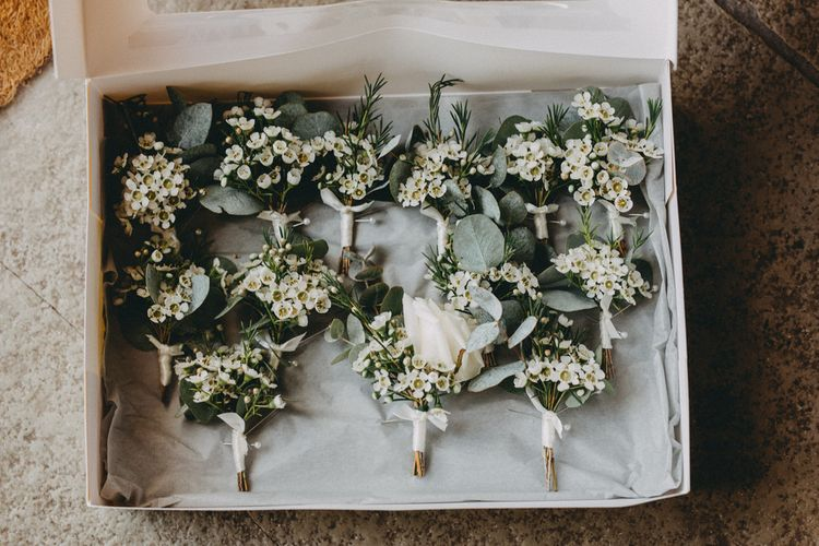 White floral buttonholes at Farbridge wedding venue