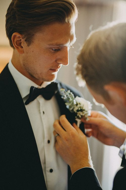 Groom in black tuxedo with white floral buttonhole
