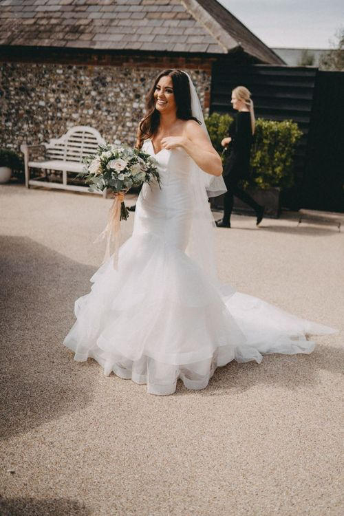 Strapless fishtail wedding dress with blush bouquet