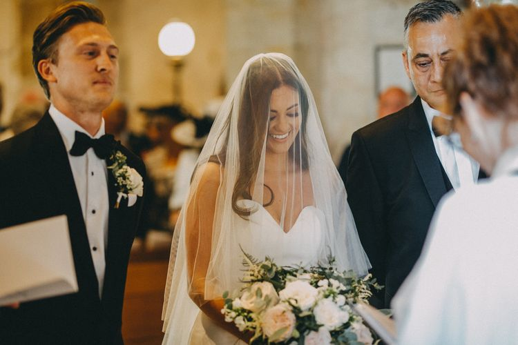 Bride greets groom at altar with veil over face