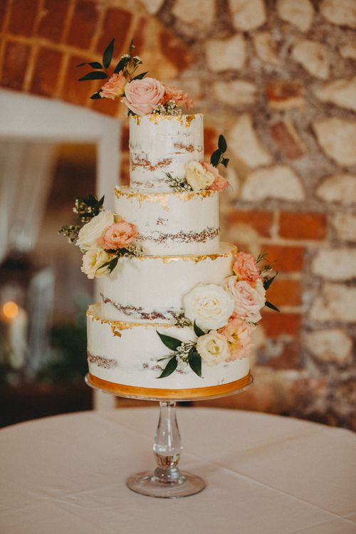 Beautiful semi-naked wedding cake with copper detail and floral decor