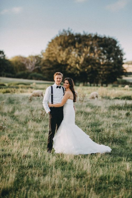Bride in strapless fishtail wedding dress with groom in tuxedo
