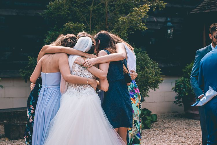 Group Hug | Bride in Beaded Halterneck Gown with Tulle Skirt and Spaghetti Straps by Maggie Sottero | Full Length Veil | Halterneck Maggie Sottero Dress and Garden Games at Gate Street Barn | Story + Colour Photography
