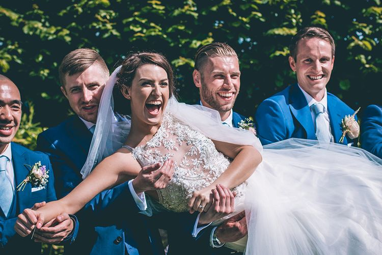Bride in Beaded Halterneck Gown with Tulle Skirt and Spaghetti Straps by Maggie Sottero | Full Length Veil | Groomsmen in Navy Blue Suits with Pastel Blue Ties | Halterneck Maggie Sottero Dress and Garden Games at Gate Street Barn | Story + Colour Photography