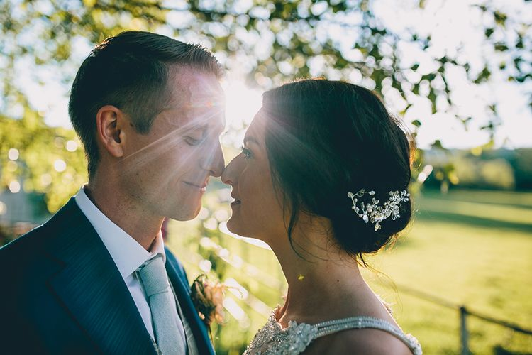 Bride in Beaded Halterneck Gown with Tulle Skirt and Spaghetti Straps by Maggie Sottero | Groom in Royal Blue Suit and Pastel Blue Tie from Suit Supply | Hair Vine from Etsy | Halterneck Maggie Sottero Dress and Garden Games at Gate Street Barn | Story + Colour Photography