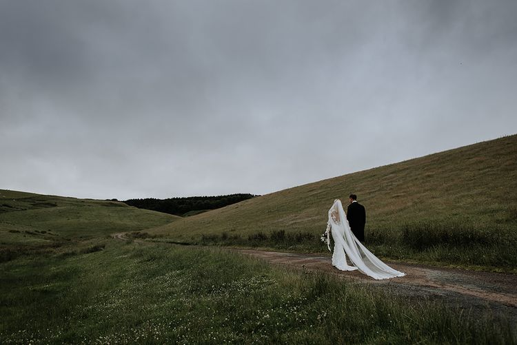 Bride and Groom In Countryside with Veil