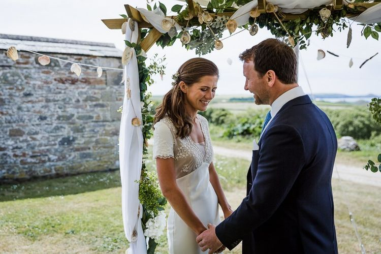 stretch tent wedding ceremony with DIY wooden altar covered in drapes, ivy and sea shells