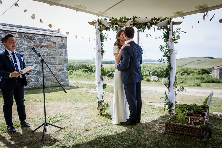 Bride and groom kissing at outdoor stretch tent wedding ceremony