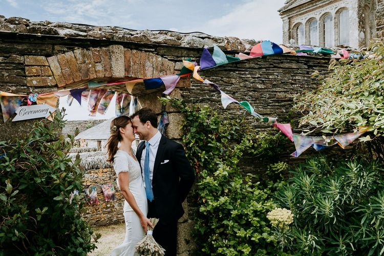 Bride and groom portrait next to their DIY wedding bunting