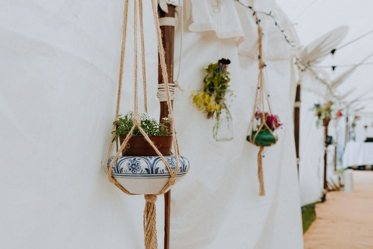 Hanging plant pots in macrame decorating the stretch tent reception