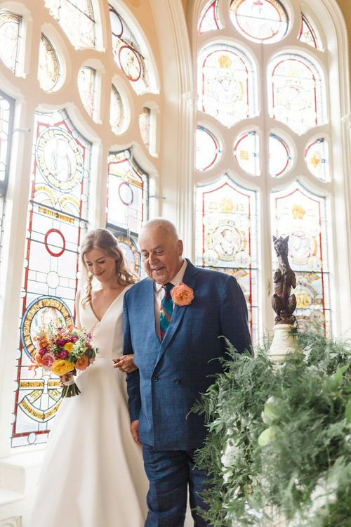 Bride walks to wedding ceremony with father and bright bouquet