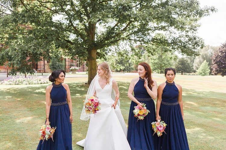 Navy bridesmaid dresses with bright flower bouquets