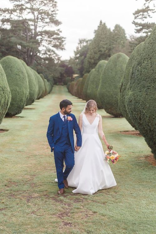 Groom in navy three piece suit with pink flower buttonhole