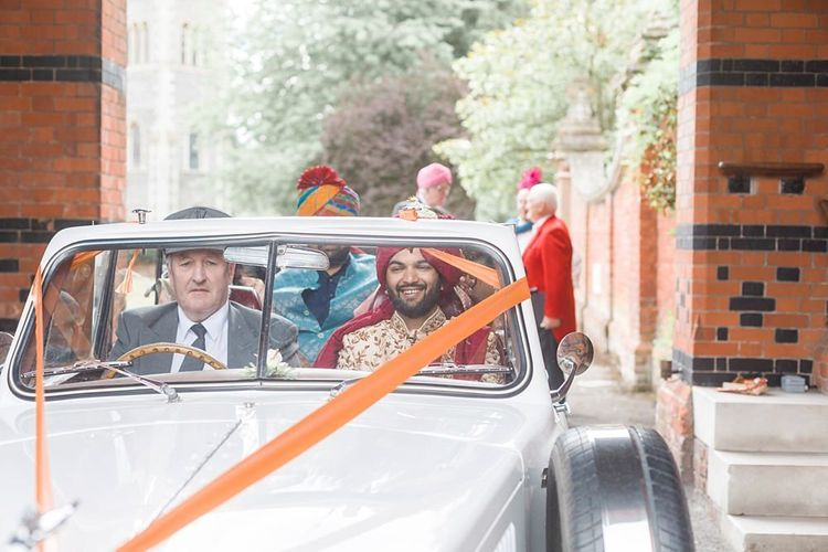 Groom arrives at Hindu wedding ceremony in vintage wedding car