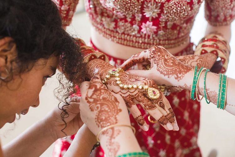 Bride gets ready in red and gold traditional Indian wedding dress