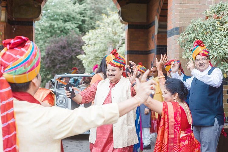 Friends and family dance as groom arrives at Hindu wedding ceremony