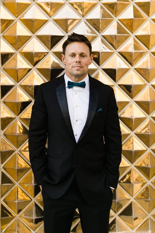 Groom in Black Tuxedo with Emerald Green Bow Tie | Las Vegas Wedding with Gold Sequin Bridesmaids Dresses and Silk Flowers | Chris Barber Photography
