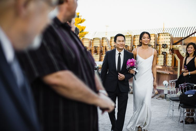 Bride in Silk BHLDN Dress with Spaghetti Straps and V-Back | Bridal Ponytail | Fuschia Sweet Pea Spray Silk Flowers Bouquet | Entrance of the Bride | Father of the Bride in Black Suit | Las Vegas Wedding with Gold Sequin Bridesmaids Dresses and Silk Flowers | Chris Barber Photography
