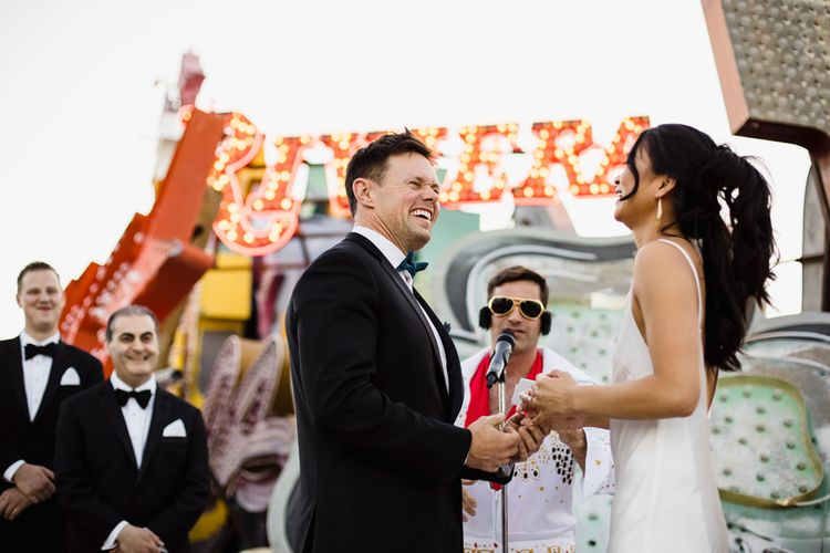 Bride in Silk BHLDN Dress with Spaghetti Straps and V-Back | Groom in Black Tuxedo with Emerald Green Bow Tie | Elvis Presley Celebrant | Groomsmen in Black Tuxedos | Wedding Ceremony at The Neon Museum | Las Vegas Wedding with Gold Sequin Bridesmaids Dresses and Silk Flowers | Chris Barber Photography
