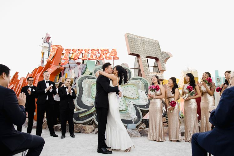 Bride in Silk BHLDN Dress with Spaghetti Straps and V-Back | Groom in Black Tuxedo with Emerald Green Bow Tie | Bridesmaids in Gold Sequin Maxi Dresses with Cowl Back | Fuschia Sweet Pea Spray Silk Flower Bouquets | Groomsmen in Black Tuxedos | Wedding Ceremony at The Neon Museum | Las Vegas Wedding with Gold Sequin Bridesmaids Dresses and Silk Flowers | Chris Barber Photography