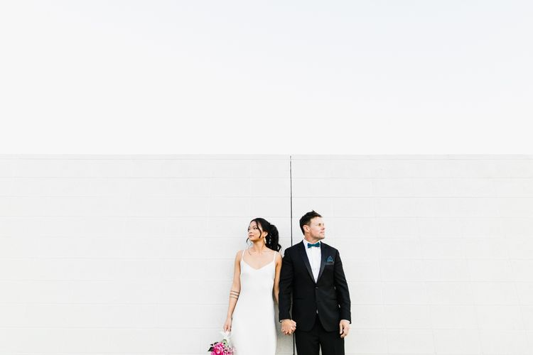 Bride in Silk BHLDN Dress with Spaghetti Straps and V-Back | Groom in Black Tuxedo with Emerald Green Bow Tie | Fuschia Sweet Pea Spray Silk Flowers Bouquet | Bridal Ponytail | Las Vegas Wedding with Gold Sequin Bridesmaids Dresses and Silk Flowers | Chris Barber Photography