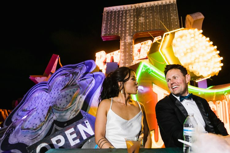 Bride in Silk BHLDN Dress with Spaghetti Straps and V-Back | Groom in Black Tuxedo with Emerald Green Bow Tie | Bridal Ponytail | The Neon Museum | Las Vegas Wedding with Gold Sequin Bridesmaids Dresses and Silk Flowers | Chris Barber Photography