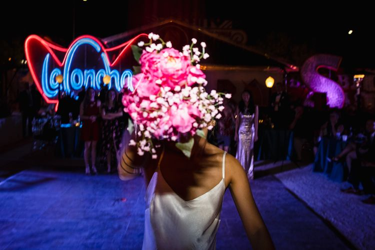 Fuschia Sweet Pea Spray Silk Flowers Bouquet | Bride in Silk BHLDN Dress with Spaghetti Straps and V-Back | Bouquet Toss | The Neon Museum | Las Vegas Wedding with Gold Sequin Bridesmaids Dresses and Silk Flowers | Chris Barber Photography