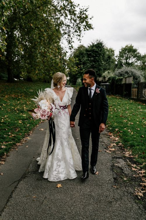 Stylish Bride and Groom Portrait by Epic Love Story with Ruffle Wedding Dress and Navy Suit