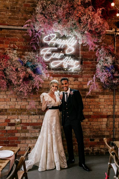 Bride and Groom Standing Under a Happily Ever After Neon Sign